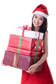 Young woman in a Santa hat carrying wrapped Christmas presents